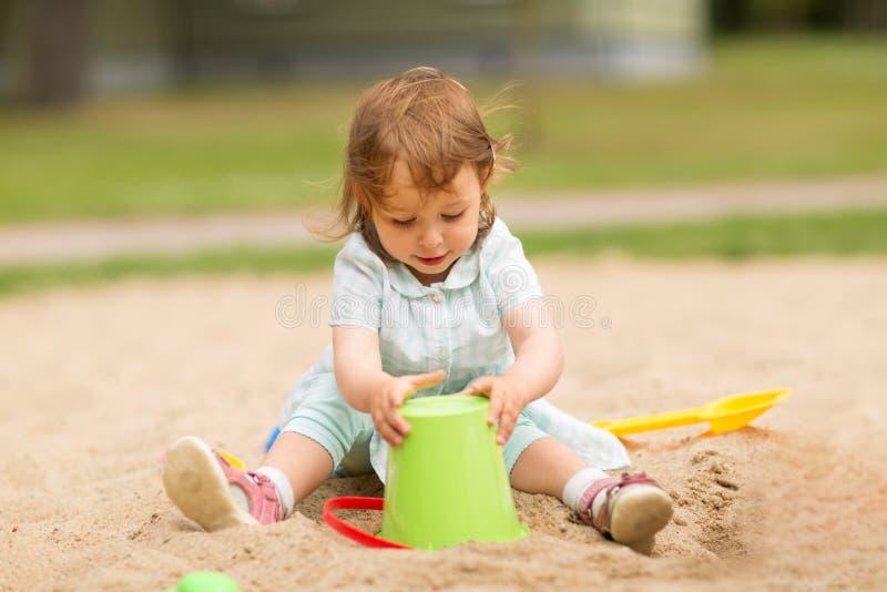 Poco juegos del bebé con los juguetes en salvadera imagen de archivo libre de regalías