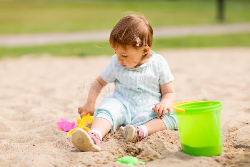 Poco juegos del bebé con los juguetes en salvadera foto de archivo libre de regalías