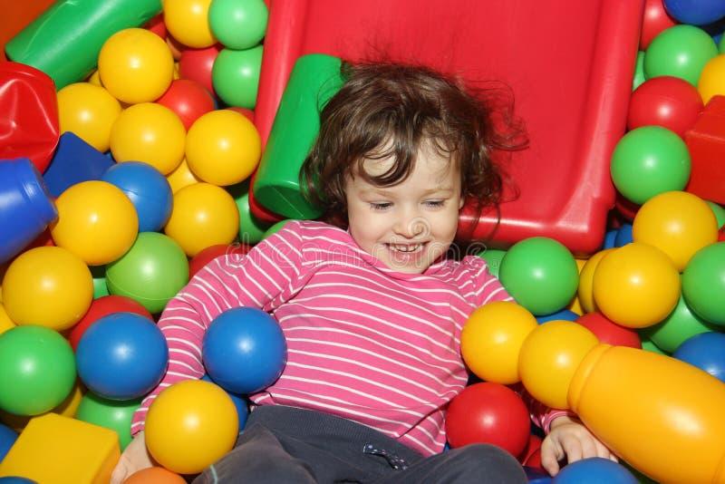 Poco juegos lindos rizados de la muchacha de la sonrisa en las bolas para una piscina seca Sitio del juego felicidad fotos de archivo libres de regalías