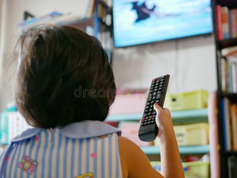 Poco la mano del bebé asiático que sostiene una televisión teledirigida, mientras que la mira en casa imagen de archivo