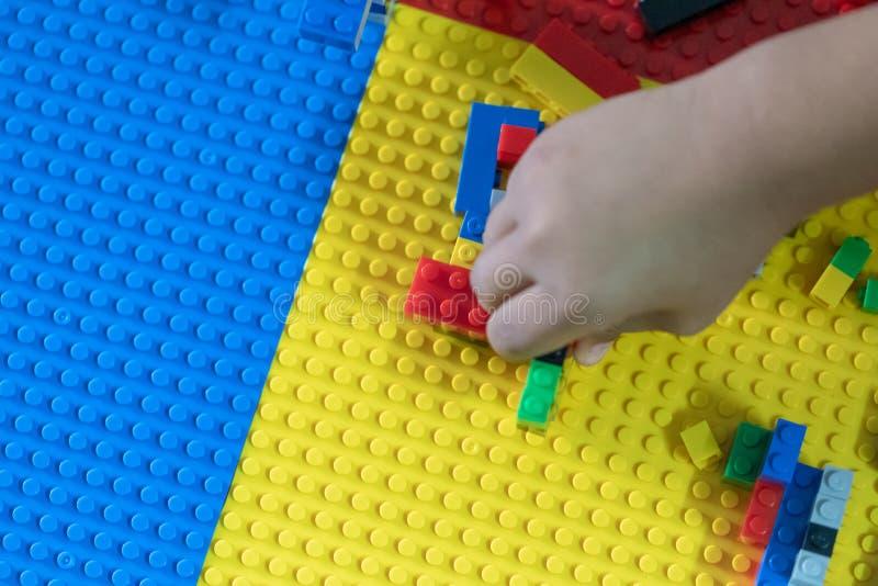 Poco los niños está jugando los juguetes en la casa fotos de archivo