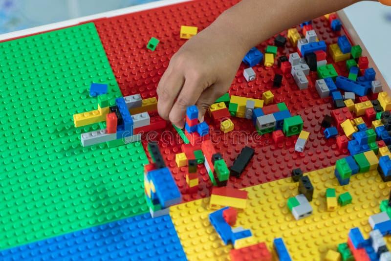Poco los niños está jugando los juguetes en la casa imagenes de archivo
