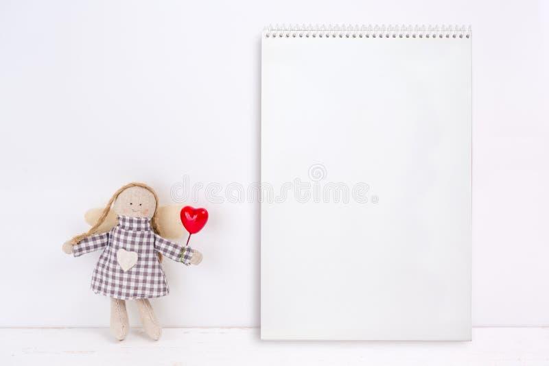 Poco marioneta con un corazón rojo y un cuaderno foto de archivo libre de regalías