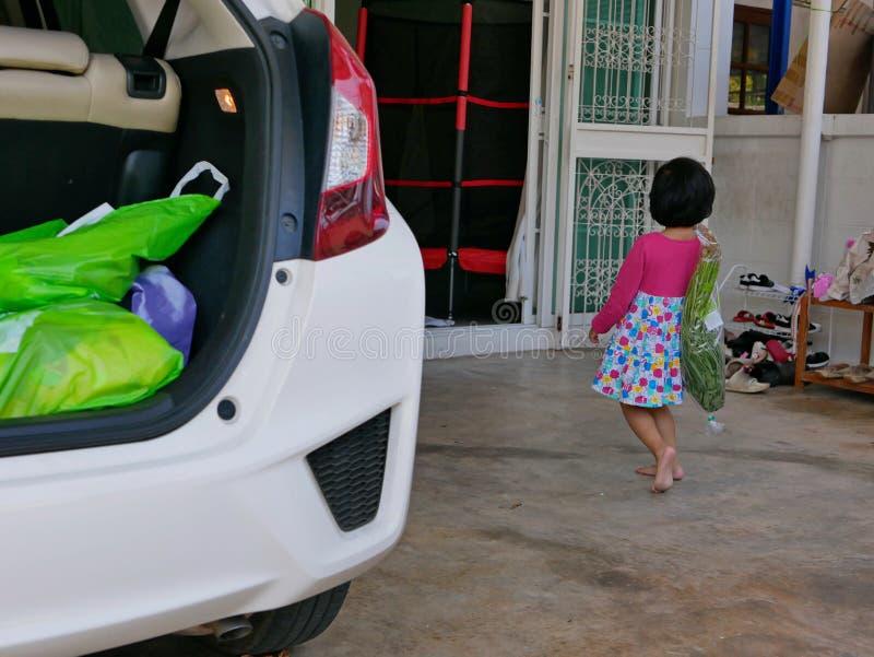 Poco materia que lleva de la ayuda asiática del bebé desde detrás del coche en la casa imagen de archivo libre de regalías