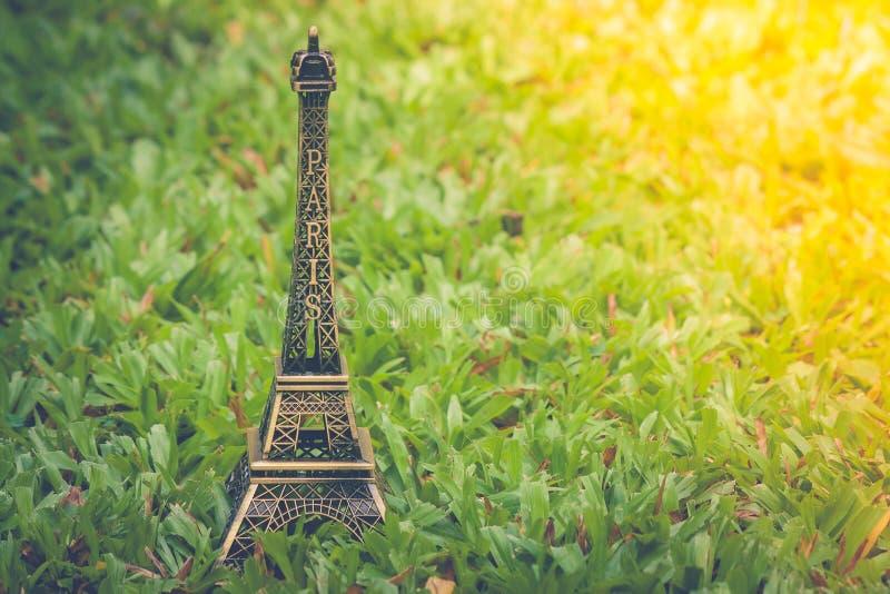 Poco modelo de la torre Eiffel en hierba verde en jardín al aire libre con el fondo de la luz del sol foto de archivo libre de regalías