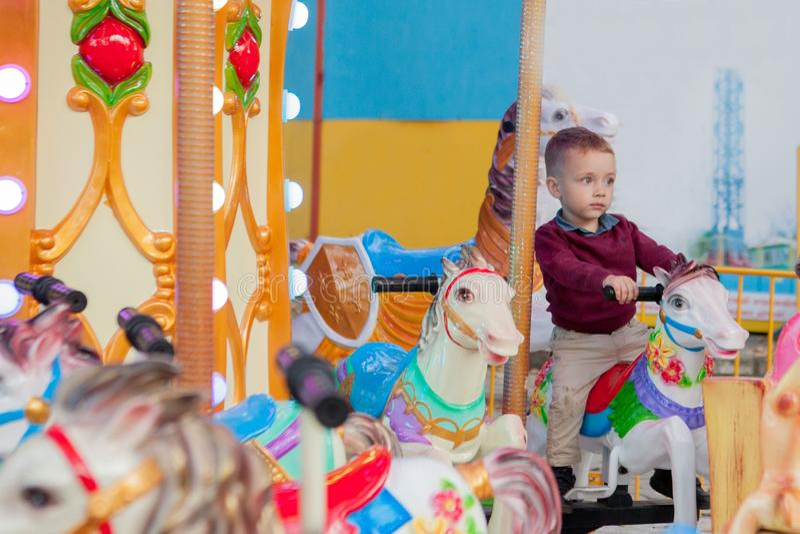 Poco montar a caballo divertido del muchacho en el caballo es un carrusel del cruce giratorio en un parque de atracciones Niño fe fotos de archivo libres de regalías