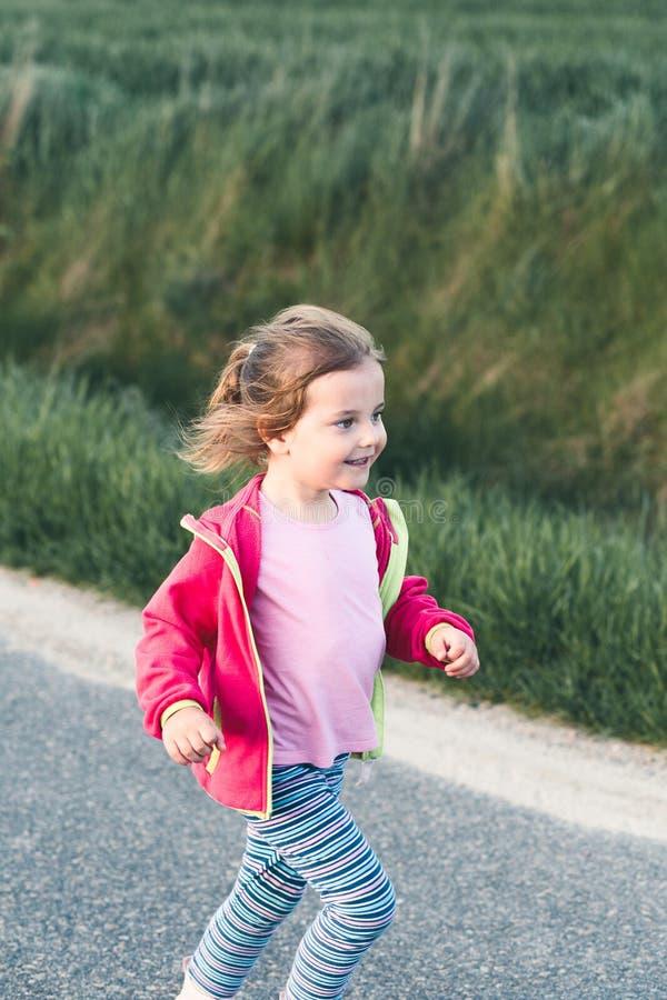 Poco muchacha adorable que se divierte que corre en el camino fotos de archivo libres de regalías