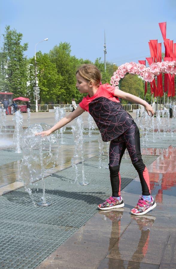 Poco muchacha adorable toca los jets de la fuente abierta de la calle foto de archivo libre de regalías