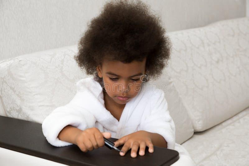 Poco muchacha afroamericana pinta clavos en las manos fotos de archivo