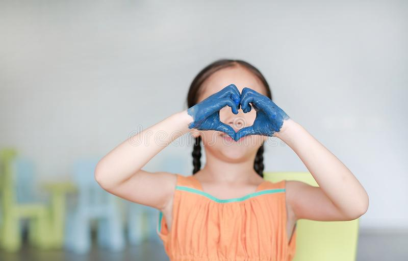 Poco muchacha asiática con sus manos azules pintó la expresión en muestra del corazón en sitio de los niños foto de archivo