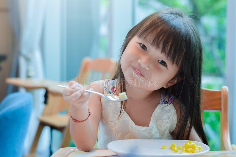 Poco muchacha asiática del niño que desayuna en la mañana con una cara sonriente feliz y que muestra la comida en una cuchara imagen de archivo
