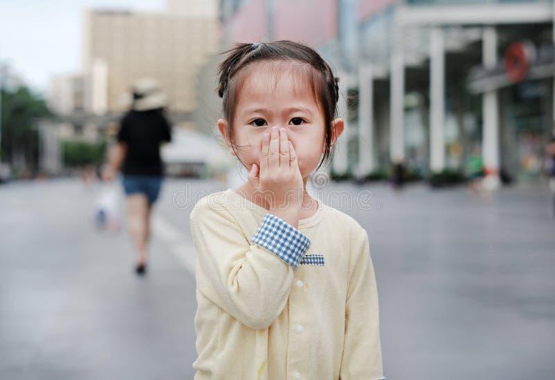 Poco muchacha asiática que cubre su boca y nariz con su mano fotos de archivo libres de regalías