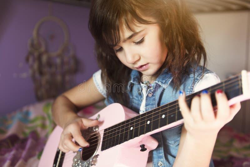 Poco muchacha atractiva con su guitarra en sus rodillas en la cama en el cuarto imagen de archivo