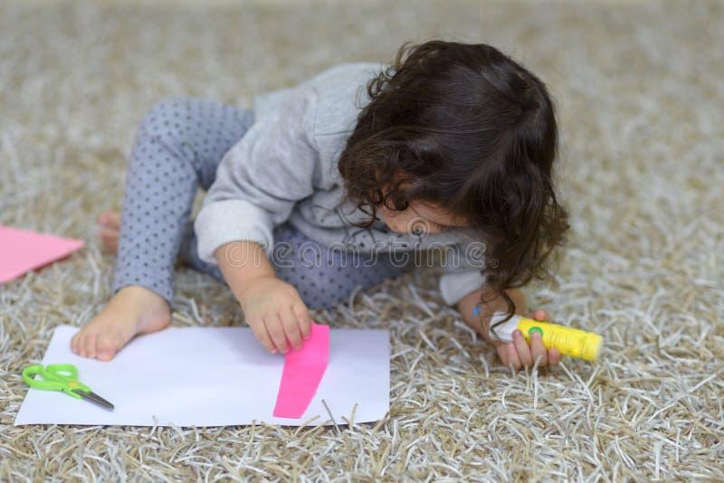 Poco muchacha del preescolar que pega el papel colorido fotos de archivo