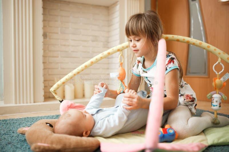 Poco muchacha encantadora mira a su hermano minúsculo que miente en la alfombra en el piso en el cuarto fotos de archivo libres de regalías
