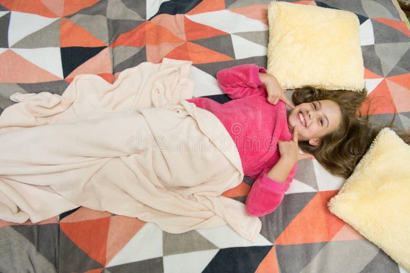 Poco muchacha feliz en dormitorio Buenos días El día de los niños internacionales Pequeño niño de la muchacha listo para dormir H fotos de archivo libres de regalías