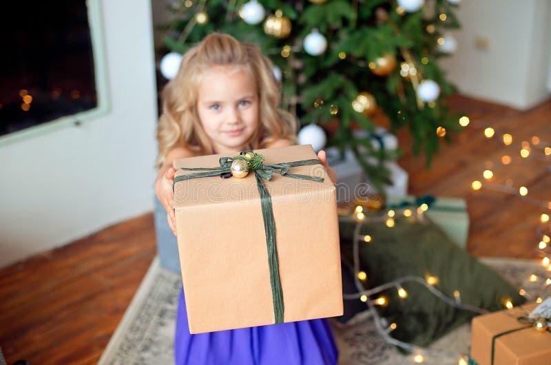 Poco muchacha hermosa con el pelo rizado rubio estira un regalo de la Navidad contra la perspectiva del árbol de navidad fotos de archivo