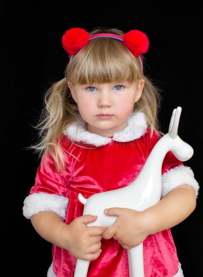 Poco muchacha hermosa en el traje de Papá Noel de la Navidad, con las bolas de la piel en su cabeza, sosteniendo un ciervo en rua imágenes de archivo libres de regalías