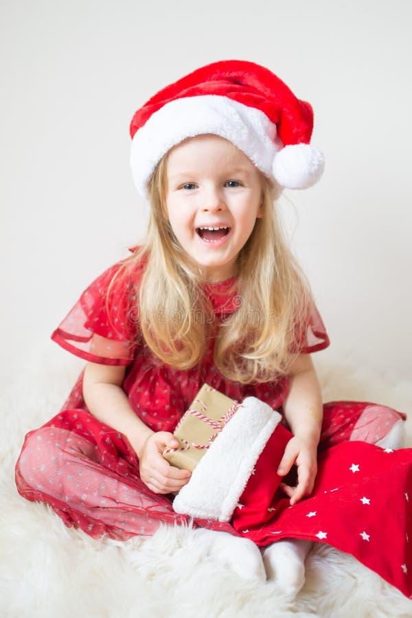 Poco muchacha hermosa en la Navidad que espera de Santa Hat Red Party Dress para y el Año Nuevo imagen de archivo