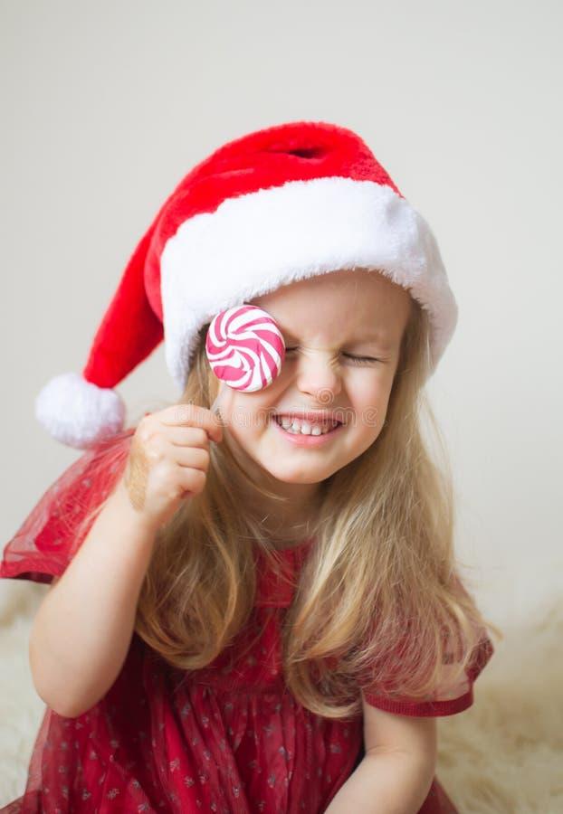 Poco muchacha hermosa en la Navidad que espera de Santa Hat Red Party Dress para y el Año Nuevo imagenes de archivo