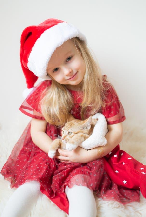 Poco muchacha hermosa en Santa Hat Red Party Dress con poco Ginger Kitten Waiting por la Navidad y el Año Nuevo fotos de archivo