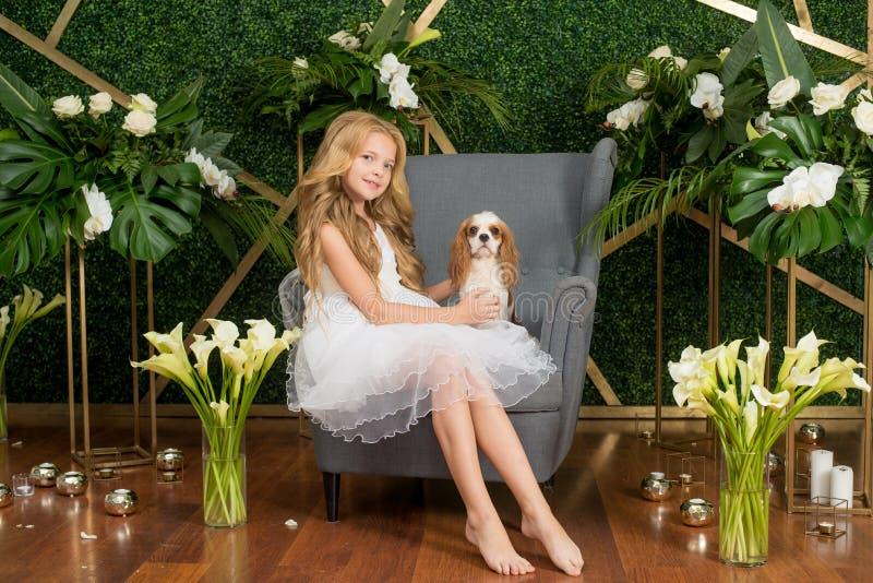 Poco muchacha linda con el pelo rubio en un vestido blanco que sostiene un pequeño perro y flores blancas, lirios y orquídeas fotos de archivo