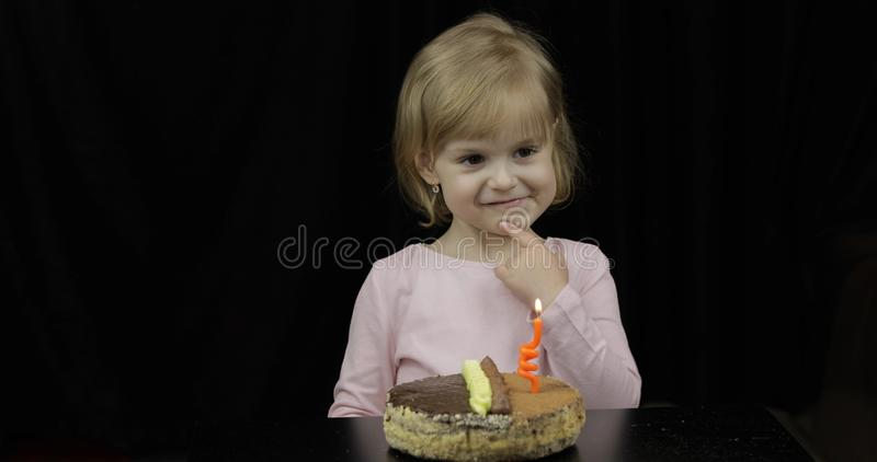 Poco muchacha linda que hace un deseo antes de vela festiva del soplo en la torta de cumpleaños foto de archivo libre de regalías