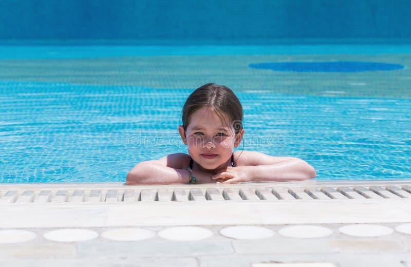 Poco muchacha linda que nada en una piscina imágenes de archivo libres de regalías