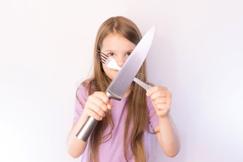 Poco muchacha linda que sostiene un cuchillo y una bifurcación de través en un fondo ligero imágenes de archivo libres de regalías