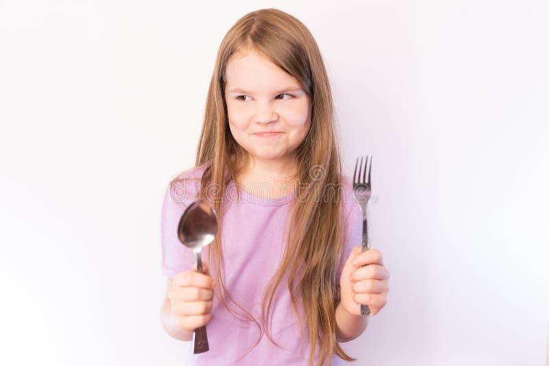 Poco muchacha linda que sostiene una cuchara y una bifurcación, sonriendo tímido en fondo ligero imagen de archivo libre de regalías