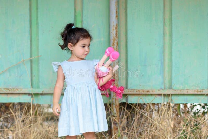 Poco muchacha morena en un vestido del color de la menta al aire libre Muñeca linda de la tenencia del niño fotos de archivo