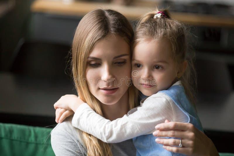 Poco muchacha preescolar que abraza a la madre cansada, trastornada imágenes de archivo libres de regalías