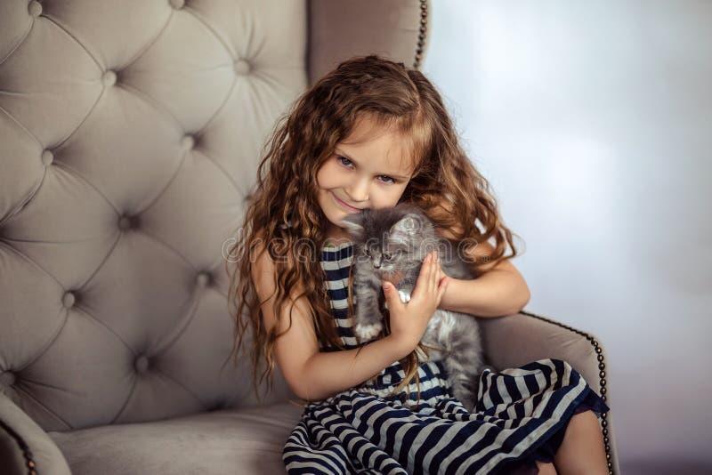 Poco muchacha rizada con un gatito gris foto de archivo libre de regalías