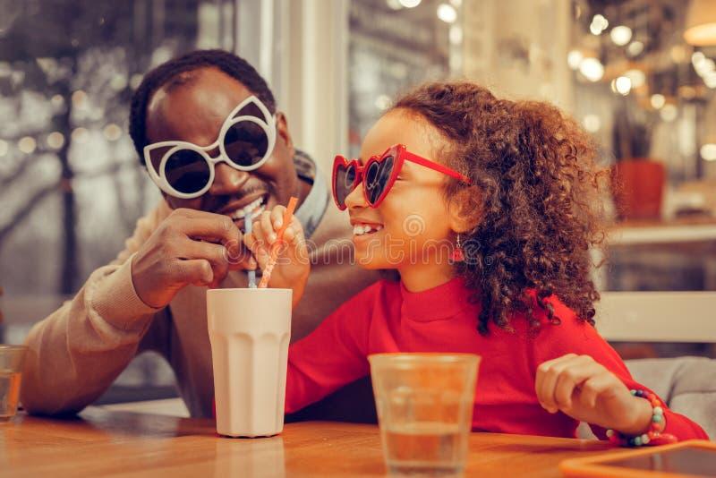 Poco muchacha rizada linda que celebra día de padres con su padre de apoyo imagenes de archivo