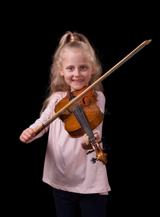 Poco muchacha rubia que toca el violín aislado en fondo negro foto de archivo