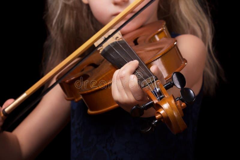 Poco muchacha rubia que toca el violín en fondo negro imágenes de archivo libres de regalías
