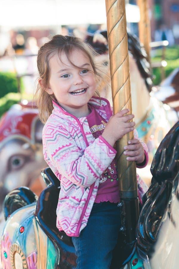 Poco muchacha sonriente adorable que monta un caballo en el carrusel del cruce giratorio en el funfair fotos de archivo