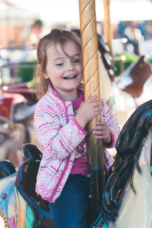 Poco muchacha sonriente adorable que monta un caballo en el carrusel del cruce giratorio en el funfair imagen de archivo