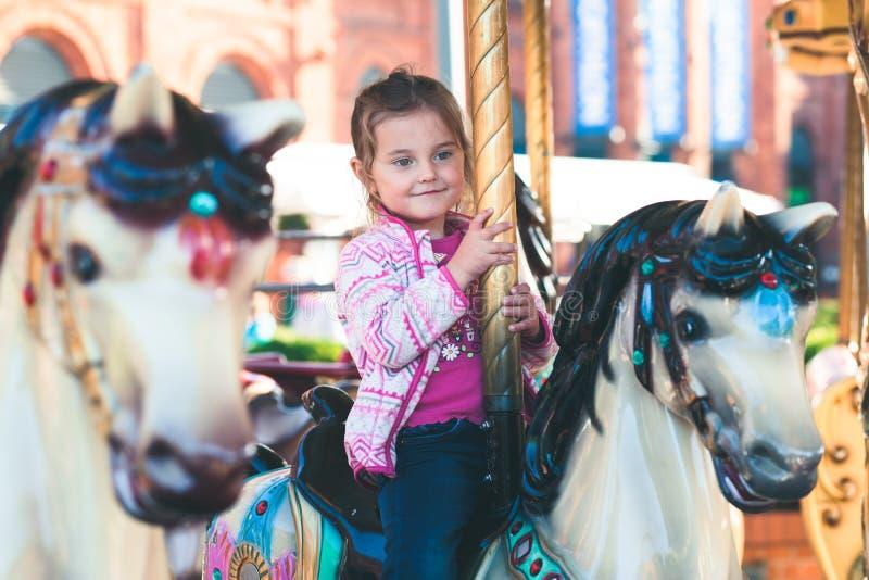 Poco muchacha sonriente adorable que monta un caballo en el carrusel del cruce giratorio en el funfair imagenes de archivo