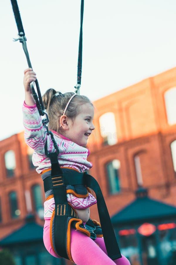 Poco muchacha sonriente adorable que salta en el trampolín, divirtiéndose en el funfair imagen de archivo libre de regalías