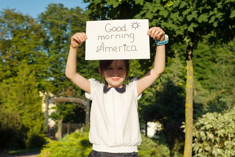 Poco muchacha sonriente con una hoja de papel blanca con el texto - Good Morning America del niño, en el parque fotos de archivo libres de regalías