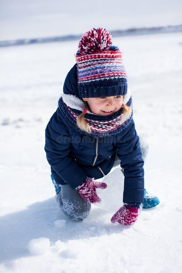 Poco muchacha sonriente en paños del invierno con hielo y nieve alrededor fotos de archivo