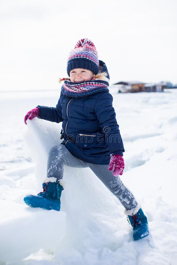 Poco muchacha sonriente en paños del invierno con hielo y nieve alrededor imágenes de archivo libres de regalías