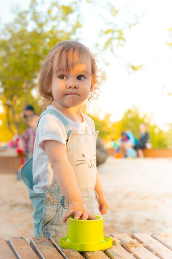 Poco muchacha sonriente que juega con la arena en salvadera en verano foto de archivo