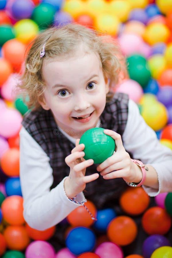Poco muchacha sonriente que se sienta entre muchas bolas coloridas - foco bajo en ojos fotografía de archivo libre de regalías