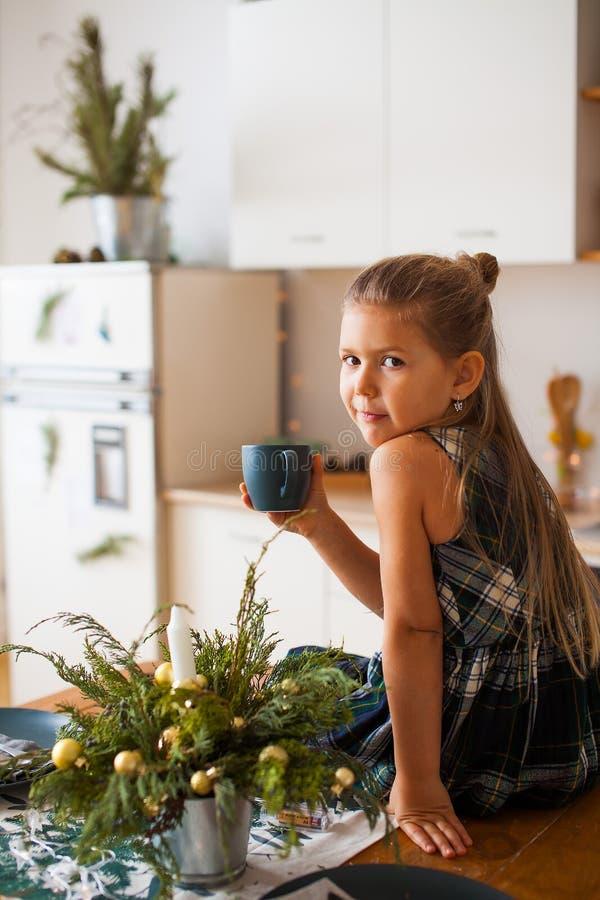 Poco muchacha sonriente que sostiene un casquillo que se sienta en la tabla en cocina en decoraciones de la Navidad fotos de archivo