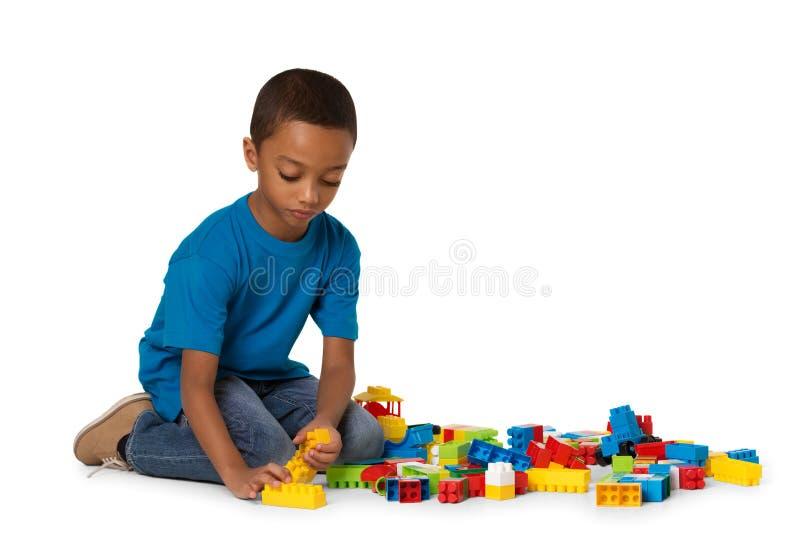 Poco muchacho africano que juega con las porciones de bloques plásticos coloridos interiores Aislado imagen de archivo