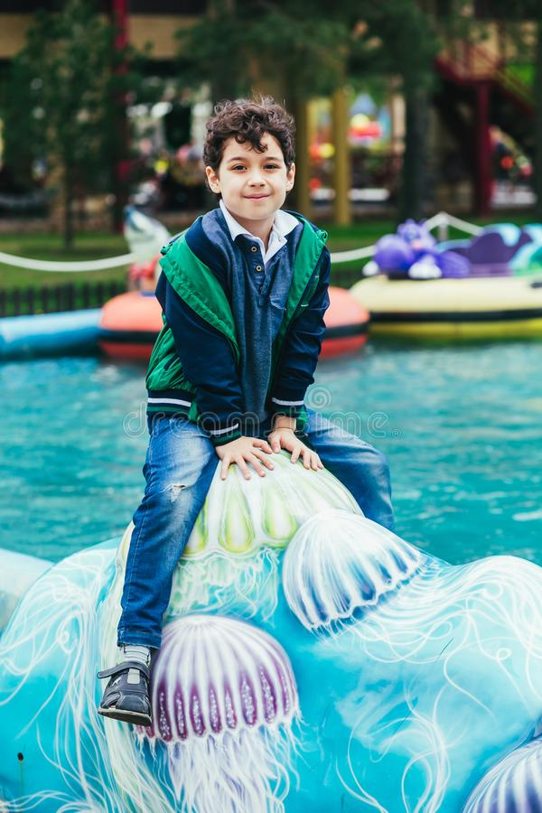 Poco muchacho bonito que se divierte al aire libre El jugar en zona de los niños en parque de atracciones foto de archivo libre de regalías