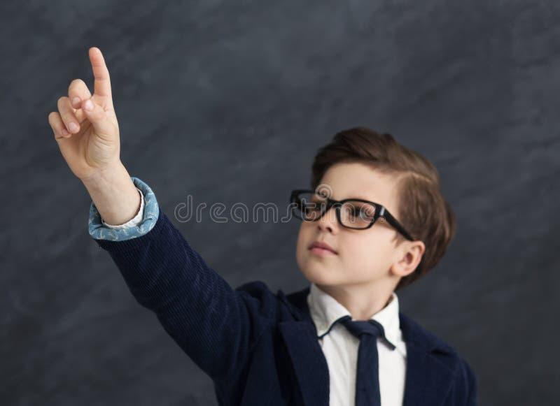 Poco muchacho del negocio que presiona el botón digital fotos de archivo