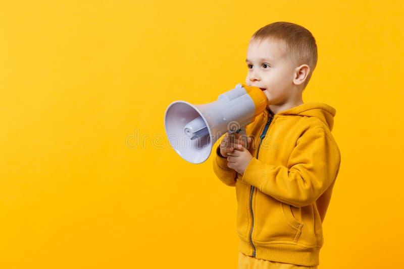 Poco muchacho del niño de la diversión 3-4 años en la ropa amarilla el sostenerse, hablando en el megáfono electrónico aislado en imagen de archivo